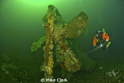 Diver explores the prop of the upside-down wreck in 42m by Mike Clark 